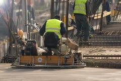 Arbetare med maskinen för konkreta trottoarer på constructioplatsen Royaltyfria Foton