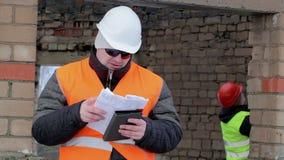 Arbetare med minnestavlaPC och dokumentation nära byggnad arkivfilmer