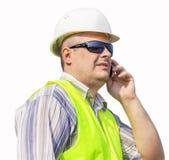 Arbetare med mobiltelefonen på en vit bakgrund Arkivfoto