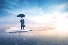 Arbetare med paraplyet på pappers- flygplan Arkivfoton