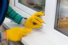 Arbetare med skruvmejsel som reparerar ett fönster Arkivfoto