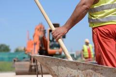 Arbetare med skyffeln på en konstruktionsplats Fotografering för Bildbyråer