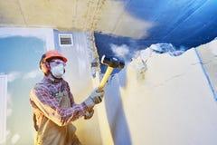 Arbetare med släggan på inomhus väggförstörelse arkivfoton