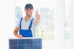 Arbetare med solpanelen som gör en gest tummar upp i ljust kontor Arkivbild