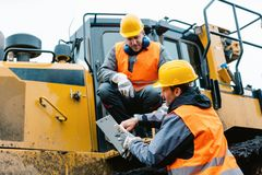 Arbetare med tungt utgrävningmaskineri i bryta operation royaltyfria bilder