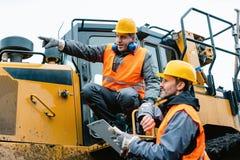 Arbetare med tungt utgrävningmaskineri i bryta operation arkivfoton