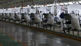 Arbetare monterar en bil på monteringsband i bilfabrik Royaltyfri Fotografi