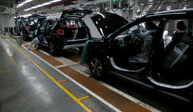 Arbetare monterar en bil på monteringsband i bilfabrik Arkivbild