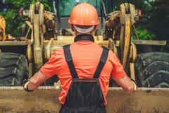 Arbetare och bulldozern arkivbild