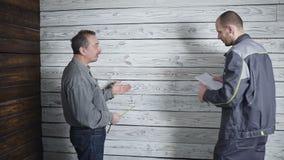 Arbetare och den fordrande kunden som ska diskuteras och sväras på bakgrunden av en trävägg Problem i konstruktion arkivfilmer