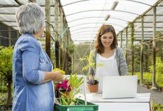 Arbetare och kund i en blomsterhandel arkivfoto