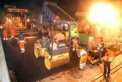 Arbetare och medel under asfaltera av huvudvägen Arkivfoton
