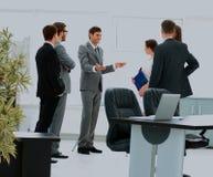 Arbetare på affärsmötet som ser presentation av finansiella rapporter i modernt kontor royaltyfria bilder