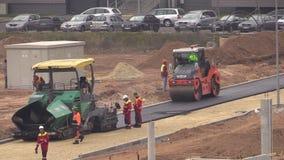 Arbetare på asfalt fördelar och rullar maskiner i plant område lager videofilmer