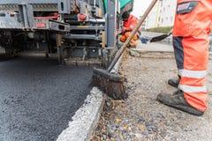 Arbetare på att asfaltera arbeten - closeup Arkivbild