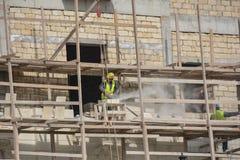 Arbetare på byggnad, vända mot av byggnaden arkivbilder