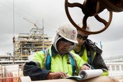 Arbetare på dokument för en kontroll för konstruktionsplats Royaltyfri Foto