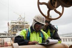 Arbetare på dokument för en kontroll för konstruktionsplats Royaltyfri Bild