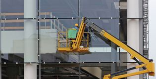 Arbetare på en körsbärsröd plockare De avslutar exponeringsglasfasaden av en byggnad under renovering royaltyfri fotografi