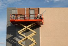 Arbetare på en körsbärsröd plockare renoverar fasaden av en byggnad, genom att applicera aluminiumpanelcladding royaltyfria bilder