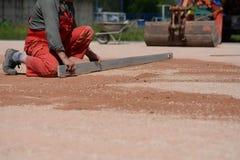Arbetare på en konstruktionsplats som försöker att jämna yttersidan Fotografering för Bildbyråer
