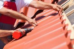Arbetare på ett tak med den elektriska drillborren som installerar den röda metalltegelplattan på trähus arkivbilder