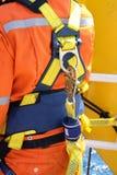 Arbetare på frånlands- med säkerhetsselet royaltyfri foto