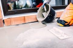 Arbetare på hällande tätningsmedel för konstruktionsplats från hinken för waterproofing cement royaltyfria bilder