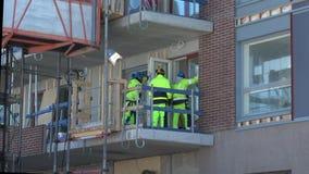 Arbetare på konstruktionen av en modern bostads- byggnad finland turku arkivfilmer