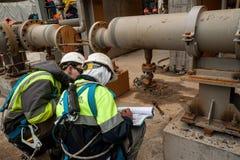 Arbetare på konstruktionsplats som kontrollerar dokument Arkivfoton
