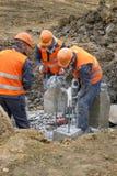 Arbetare på kotletten för konstruktionsplats som en tryckluftsborr traver klipps royaltyfri foto