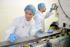 Arbetare på livsmedelsproduktionlinje royaltyfria foton