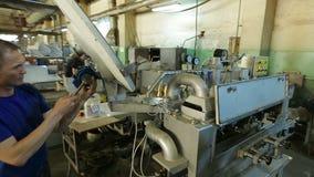 Arbetare på maskinen på fabrik arkivfilmer