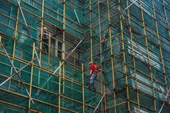 Arbetare på materialet till byggnadsställning Arkivfoton