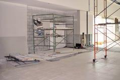 Arbetare på materialet till byggnadsställning som installerar gipsväggen royaltyfri fotografi
