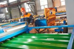 Arbetare på metallarket som profilerar fabriken Arkivfoton