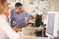 Arbetare på skrivbord i upptaget idérikt kontor Royaltyfria Foton