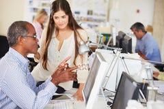 Arbetare på skrivbord i upptaget idérikt kontor Arkivfoto