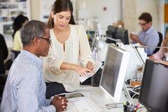 Arbetare på skrivbord i upptaget idérikt kontor Fotografering för Bildbyråer