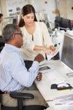 Arbetare på skrivbord i upptaget idérikt kontor Arkivbilder