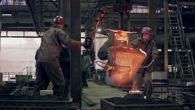 Arbetare på stålväxten fungerar med smält metall stock video