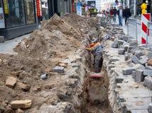 Arbetare reparerar rörledningen i ett dike Royaltyfri Foto