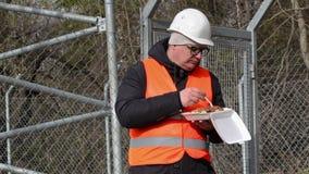 Arbetare som äter nära trådstaketet lager videofilmer