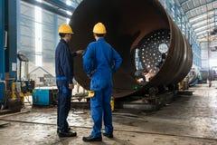 Arbetare som övervakar tillverkningen av en metallisk cylinder arkivbilder