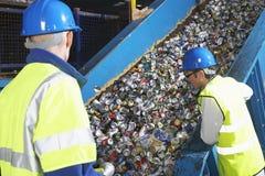 Arbetare som övervakar transportbandet av återanvända cans Royaltyfri Foto