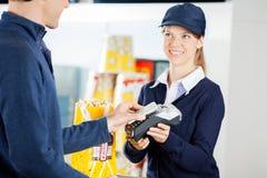 Arbetare som accepterar betalning till och med NFC-teknologi royaltyfri fotografi
