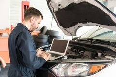 Arbetare som använder bärbara datorn för att avkänna fel i bil på garaget fotografering för bildbyråer