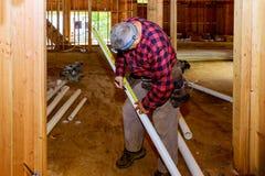 Arbetare som använder klippa special sax för plast- PVC-rör i konstruktion arkivfoto