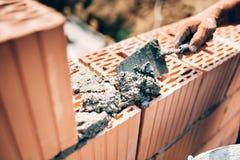 Arbetare som använder mursleven och hjälpmedel för att bygga yttre väggar med tegelstenar och mortel royaltyfria bilder