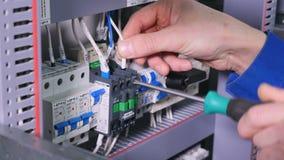 Arbetare som använder skruvmejseln på elektrisk utrustning stock video